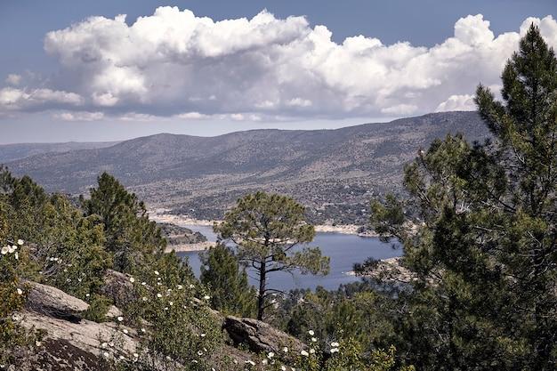 Panoramique de certaines montagnes sous un ciel bleu nuageux un matin de printemps Photo Premium