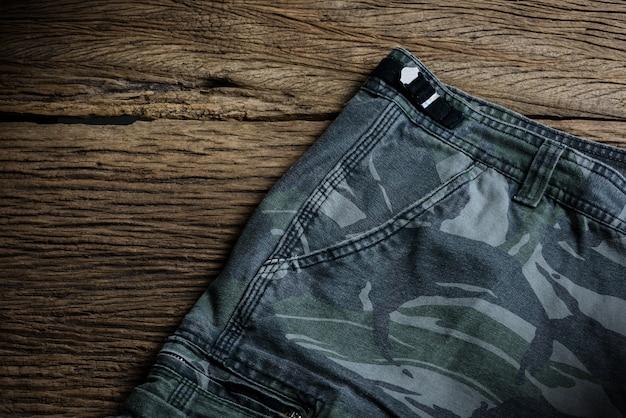 Pantalon motif camouflage sur fond en bois Photo Premium
