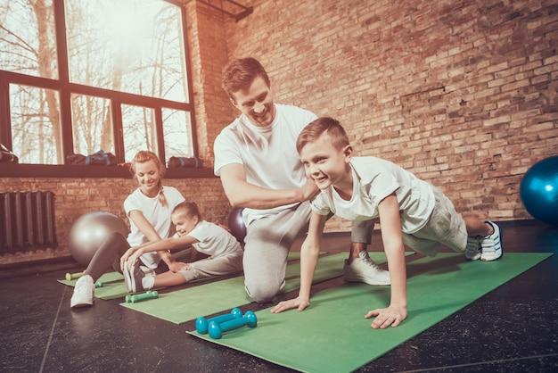 Papa apprend à son fils à pousser son fils dans une salle de sport. Photo Premium