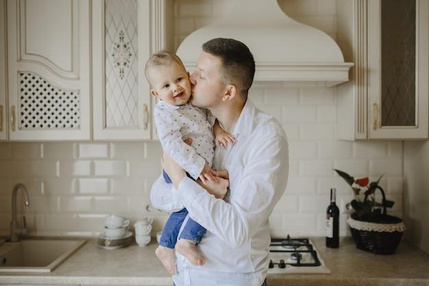 Papa embrasse bébé fils dans la cuisine Photo gratuit
