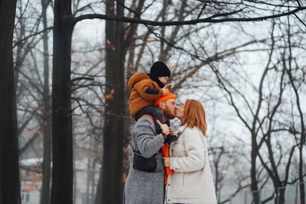 Papa maman et bébé dans le parc en hiver Photo gratuit