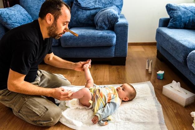 Papa nettoie le cul sale de son bébé, change la couche puante avec un pince-nez, la paternité et l'humour. Photo Premium
