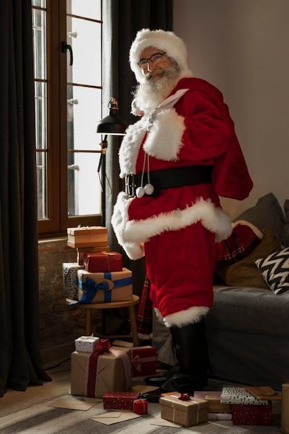 Papa noel avec le sac de cadeaux sur son épaule Photo gratuit