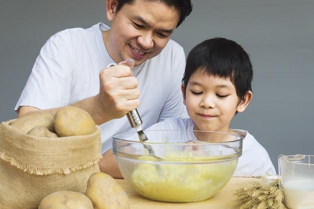 Papa et son fils font de la purée de pommes de terre Photo gratuit