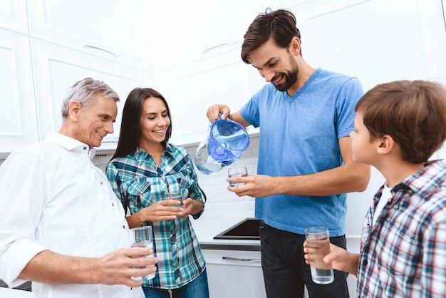 Papa verse toute l'eau de la famille à partir du filtre. Photo Premium