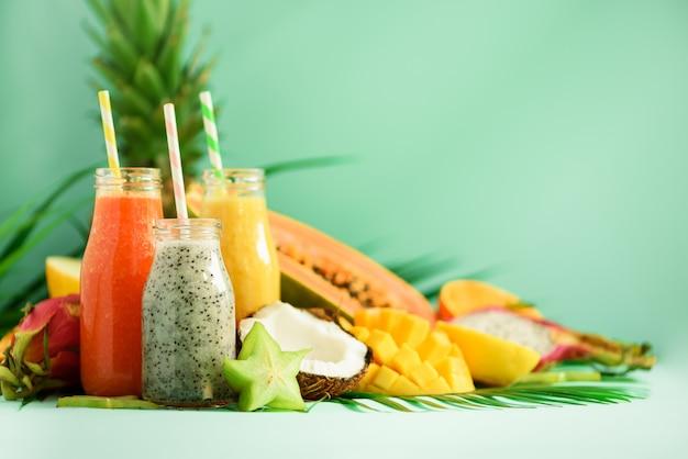 Papaye, fruit du dragon, ananas, smoothie à la mangue dans des bocaux sur fond turquoise. detox, aliment de régime végétalien, concept de saine alimentation. Photo Premium
