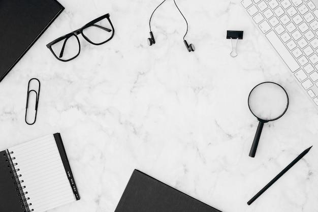 Papeterie; clavier et lunettes de vue sur fond texturé en marbre blanc Photo gratuit
