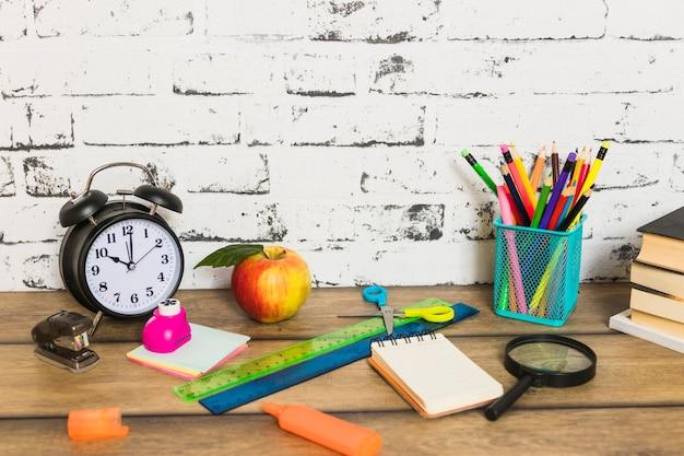 Papeterie colorée et pomme posées de manière aléatoire Photo gratuit