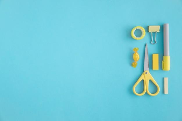 Papeterie jaune et bonbons sur fond bleu Photo gratuit