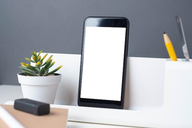 Papeterie moderne sur une table blanche et un mur gris foncé Photo Premium