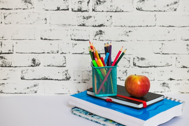 Papeterie et pomme posées sur des cahiers Photo gratuit