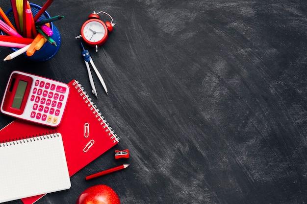 Papeterie rouge près d'horloge et de pomme sur le tableau noir Photo gratuit