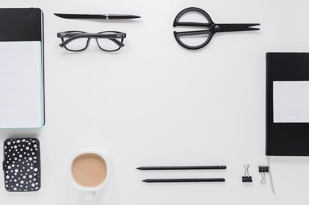 Papeterie et tasse à café près de verres sur une table blanche Photo gratuit