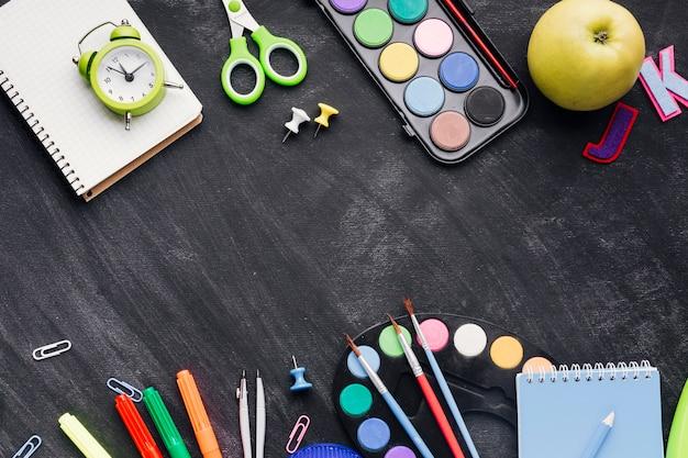 Papeterie vibrante, horloge et pomme sur fond gris Photo gratuit