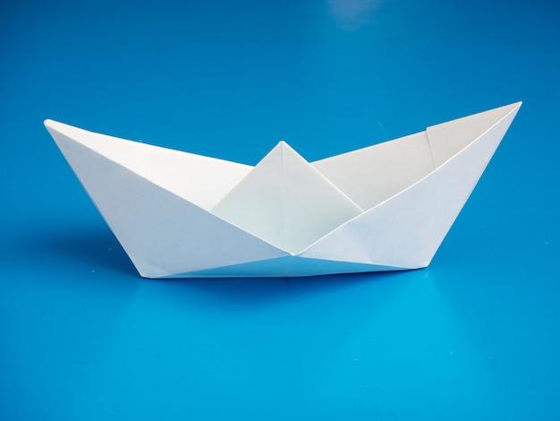 Papier de bateau blanc origami concept commercial minimal sur fond bleu Photo Premium