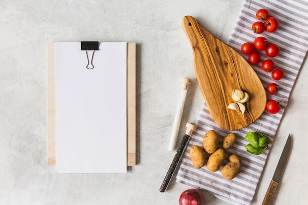 Papier blanc blanc sur le presse-papiers avec des légumes et des épices sur fond blanc Photo gratuit