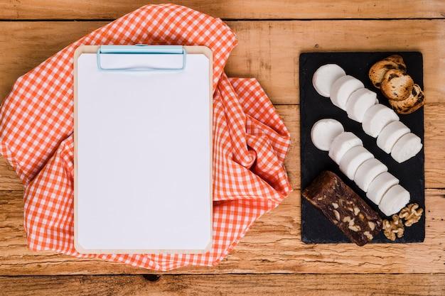 Papier blanc blanc sur le presse-papiers avec nappe près de fromage de chèvre et collation sur pierre d'ardoise Photo gratuit