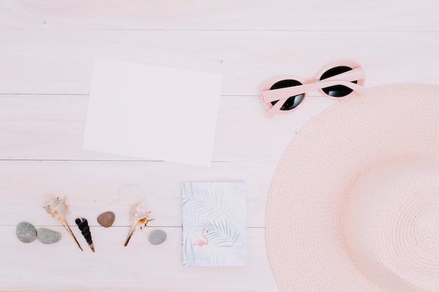 Papier blanc et choses d'été sur une surface claire Photo gratuit