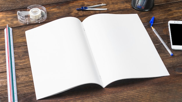 Un papier blanc ouvert avec des articles de papeterie sur une table en bois Photo gratuit