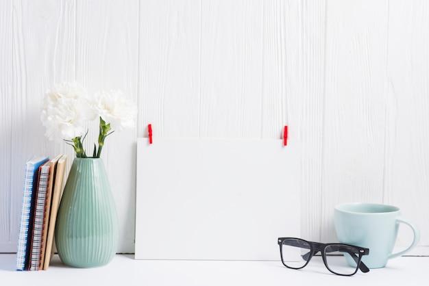 Papier blanc avec pince à linge rouge; lunettes; tasse; vase et livres sur fond texturé en bois Photo gratuit