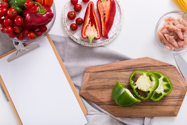 Papier blanc sur le presse-papiers avec du poivron; tomates cerises et poulet sur fond blanc Photo gratuit