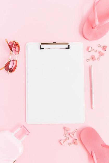 Papier blanc sur le presse-papiers entouré d'un sac de bagage miniature; des lunettes de soleil; trombones; crayon et tongs sur fond rose Photo gratuit