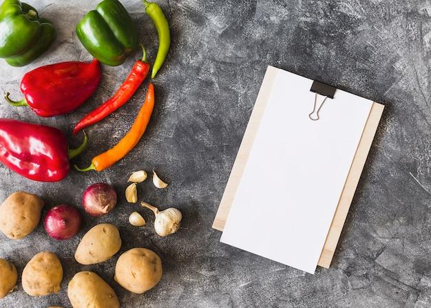 Papier blanc sur le presse-papiers avec des légumes sur fond grunge Photo gratuit