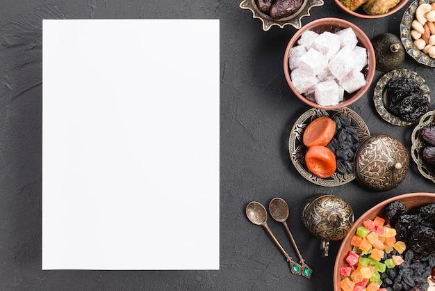 Papier blanc vierge avec des bonbons arabes; fruits secs; noix pour le ramadan sur fond noir Photo gratuit