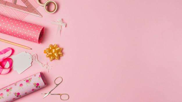 Papier cadeau; ciseaux; étiquettes et articles de papeterie sur du papier peint rose avec un espace pour le texte Photo gratuit