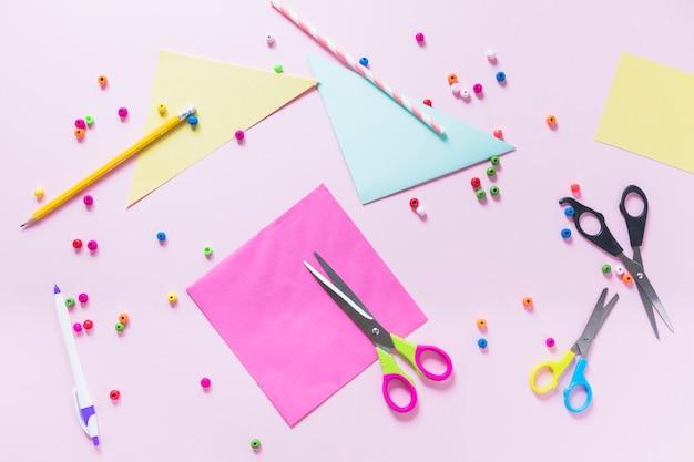 Papier coloré; crayon; stylo; perles et ciseaux sur fond rose Photo gratuit