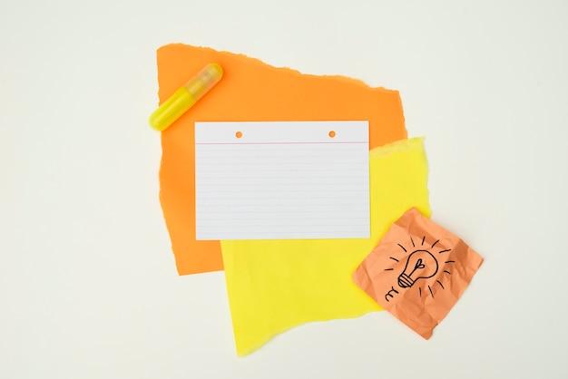 Papier de couleur et de la colle avec du papier à notes ampoule dessiné isolé sur fond blanc Photo gratuit