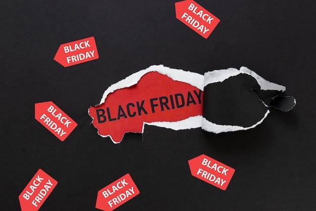 Papier déchiré révélant un texte de vendredi noir avec des autocollants Photo gratuit