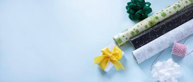 Papier D'emballage Arcs Et Ruban Prêts à Emballer Des Cadeaux Sur Fond Bleu Clair Bannière Web Avec Espace Pour Le Texte Photo Premium