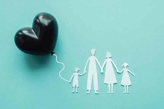 Papier de famille découpé tenant un ballon coeur noir sur fond bleu Photo Premium