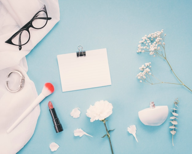 Papier avec des fleurs et des produits de beauté sur la table Photo gratuit
