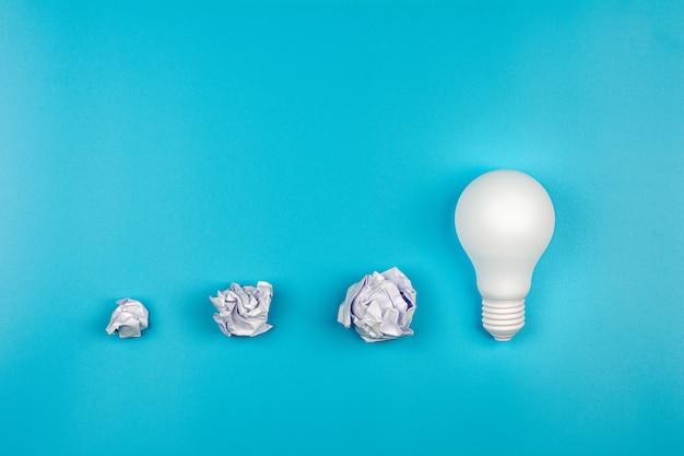 Papier froissé blanc et ampoule sur table bleue. - concept de croissance des affaires et de bonnes idées. Photo Premium