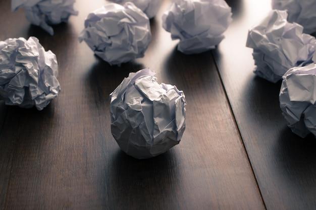 Papier froissé sur fond de bois. frustrations commerciales, stress au travail et concept d'examen ayant échoué. Photo Premium