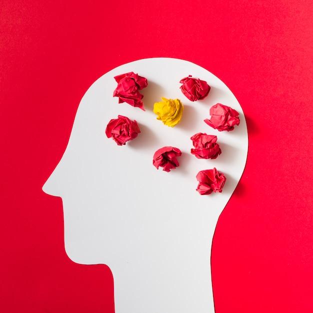 Papier froissé sur la tête humaine blanche découpée sur fond rouge Photo gratuit