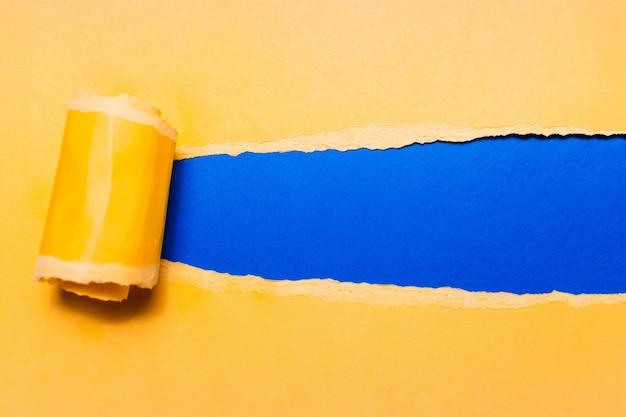 Papier Jaune Déchiré En Diagonale Avec Un Espace Pour Le Texte De Fond Bleu. Photo Premium