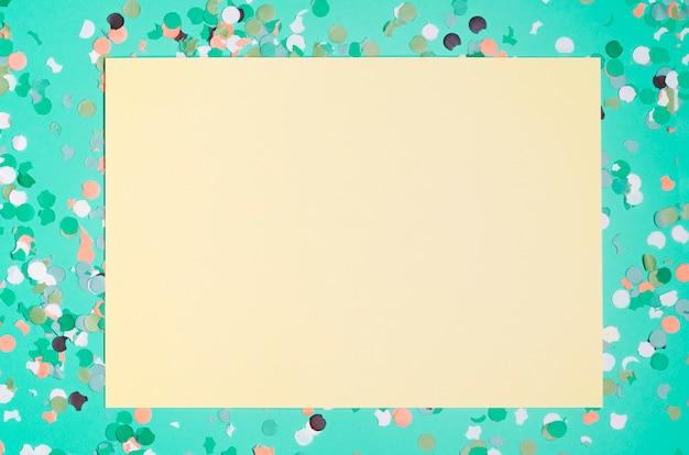 Papier jaune vierge avec des confettis colorés sur fond vert Photo gratuit