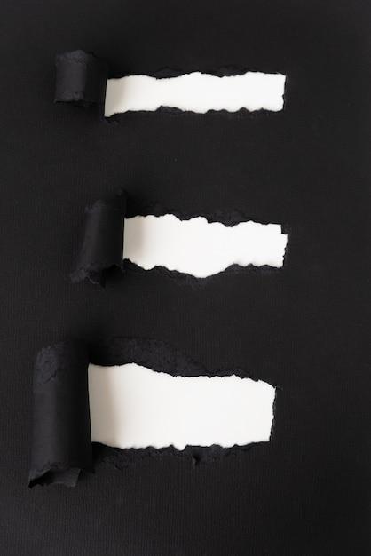 Papier noir déchiré révélant le blanc Photo gratuit