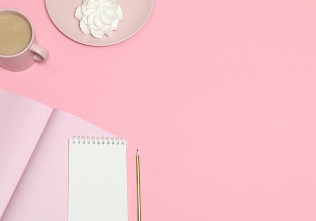 Papier à notes rose, tasse à café, gâteau sur fond rose Photo Premium