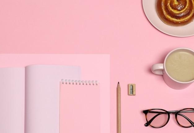 Papier à notes roses, crayon en bois, taille-crayon, tasse à café, gâteau sur fond rose Photo Premium