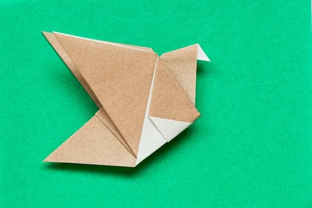 Papier Origami Brun En Forme D'oiseau En Vol Sur Fond Vert Photo Premium