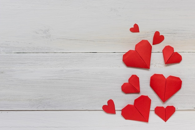 Papier origami coeur rouge sur fond en bois blanc, romance et concept de la saint-valentin Photo Premium