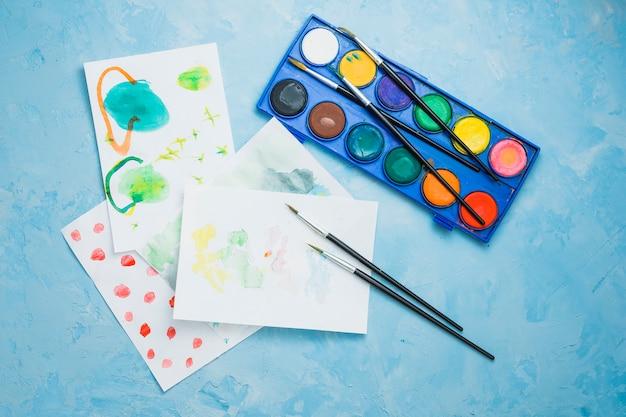 Papier peint et des fournitures de peinture à la main sur un fond bleu texturé Photo gratuit