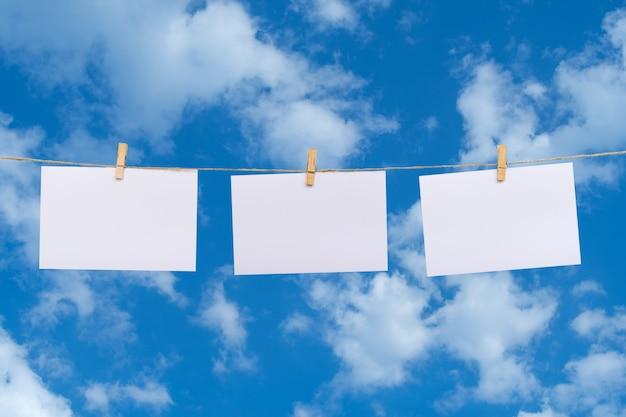 Papier photo blanc suspendu à une corde à linge au-dessus des nuages dans le fond de ciel bleu Photo Premium