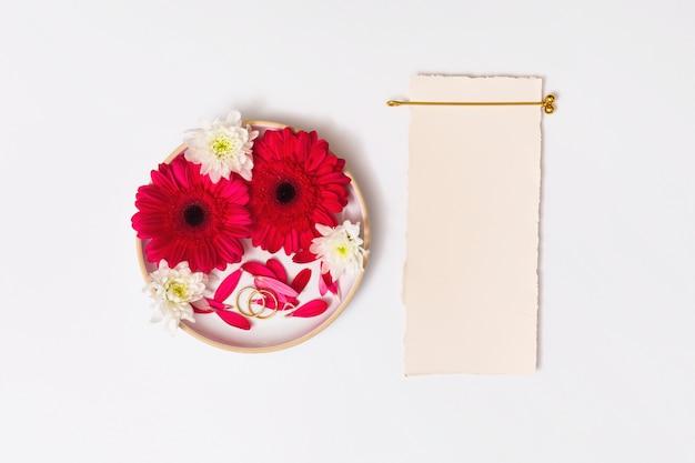 Papier près des anneaux et ensemble de fleurs fraîches en rond Photo gratuit