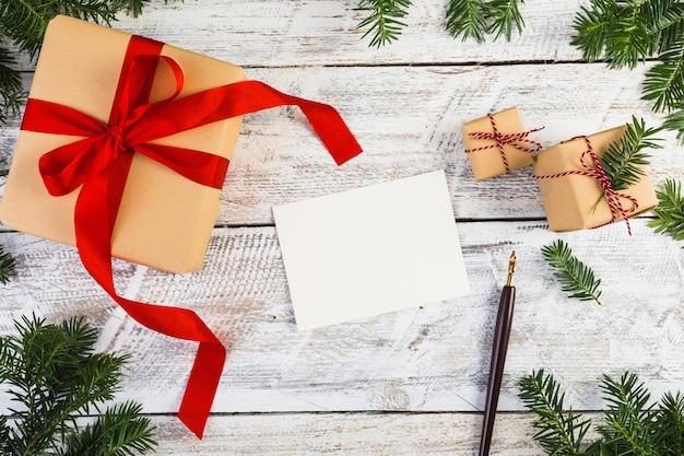 Papier près de brindilles de sapin, stylos et boîtes à cadeaux Photo gratuit