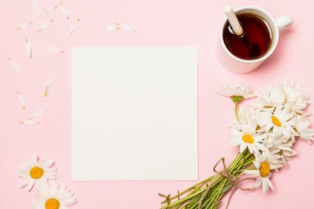 Papier Près De Fleurs Et Tasse De Boisson Photo gratuit